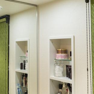Diseño de aseo asiático con paredes blancas, lavabo integrado, suelo marrón, suelo de contrachapado y puertas de armario blancas