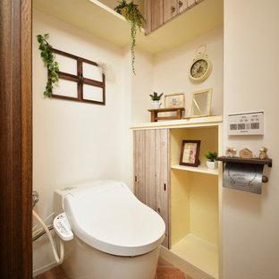 他の地域の北欧スタイルのおしゃれなトイレ・洗面所 (フラットパネル扉のキャビネット、ヴィンテージ仕上げキャビネット、白い壁、テラコッタタイルの床、茶色い床) の写真