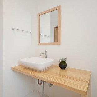 На фото: маленький туалет в восточном стиле с открытыми фасадами, бежевыми фасадами, раздельным унитазом, белой плиткой, каменной плиткой, красными стенами, полом из винила, врезной раковиной, столешницей из дерева, белым полом и бежевой столешницей