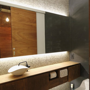Photo of a world-inspired cloakroom in Other with flat-panel cabinets, distressed cabinets, grey walls, a vessel sink and white floors.
