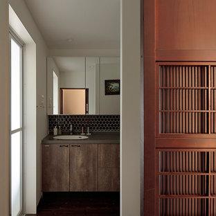 Неиссякаемый источник вдохновения для домашнего уюта: туалет среднего размера в стиле ретро с коричневой плиткой, керамогранитной плиткой, белыми стенами, темным паркетным полом, врезной раковиной, столешницей из искусственного камня, коричневым полом и черной столешницей