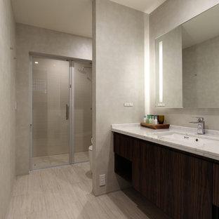 他の地域の中くらいのモダンスタイルのおしゃれなトイレ・洗面所 (フラットパネル扉のキャビネット、茶色いキャビネット、一体型トイレ、ベージュのタイル、ベージュの壁、セラミックタイルの床、アンダーカウンター洗面器、人工大理石カウンター、ベージュの床、白い洗面カウンター) の写真