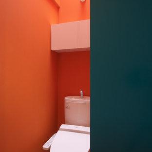 Immagine di un bagno di servizio contemporaneo con pareti arancioni e parquet chiaro