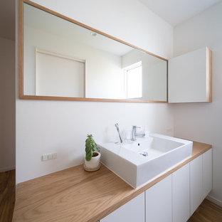 Diseño de aseo asiático con puertas de armario blancas, paredes blancas, suelo de madera clara, lavabo tipo consola, armarios con paneles lisos, encimera de madera, suelo marrón y encimeras beige