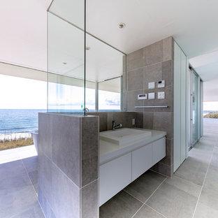 他の地域の広いモダンスタイルのおしゃれなトイレ・洗面所 (磁器タイルの床、グレーの床、フラットパネル扉のキャビネット、白いキャビネット、白い壁、オーバーカウンターシンク) の写真