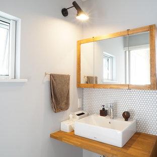 他の地域の小さい北欧スタイルのおしゃれなトイレ・洗面所 (オープンシェルフ、白いタイル、青い壁、ベッセル式洗面器、グレーの床) の写真