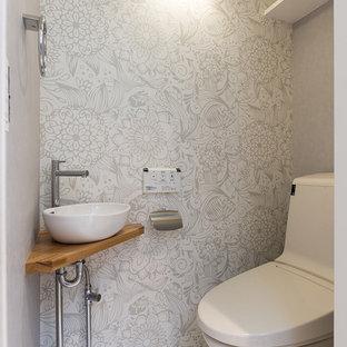 Ejemplo de aseo actual con sanitario de una pieza, paredes grises, suelo de contrachapado, lavabo tipo consola y suelo blanco