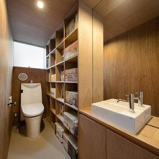 東京23区のコンテンポラリースタイルのおしゃれなトイレ・洗面所 (フラットパネル扉のキャビネット、中間色木目調キャビネット、茶色い壁、ベッセル式洗面器、木製洗面台、グレーの床、ブラウンの洗面カウンター) の写真