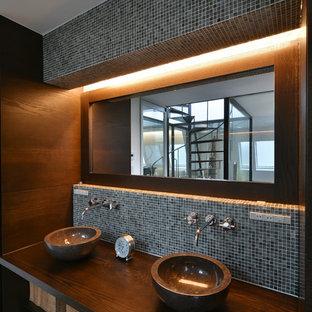 Идея дизайна: туалет в стиле лофт с консольной раковиной, синей плиткой, черной плиткой и коричневыми стенами