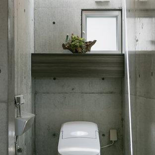 Diseño de aseo de estilo zen con paredes grises, lavabo suspendido y suelo gris