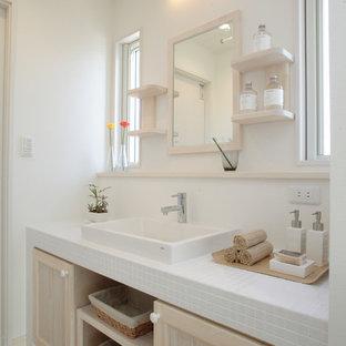Aménagement d'un WC et toilettes scandinave avec un placard avec porte à panneau encastré, des portes de placard beiges, un mur blanc, une vasque, un plan de toilette en carrelage, un sol beige et un plan de toilette blanc.