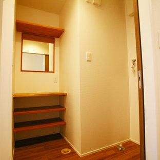 Minimalistisk inredning av ett mellanstort vit vitt toalett, med luckor med profilerade fronter, skåp i mellenmörkt trä, en toalettstol med hel cisternkåpa, vita väggar, mellanmörkt trägolv, ett fristående handfat och brunt golv