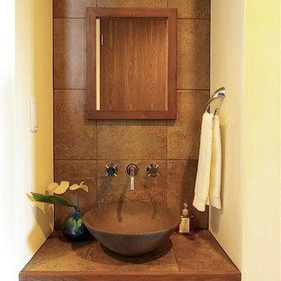 他の地域, のミッドセンチュリースタイルのおしゃれなトイレ・洗面所 (茶色いキャビネット、茶色いタイル、磁器タイル、白い壁、無垢フローリング、タイルの洗面台、茶色い床、ブラウンの洗面カウンター) の写真