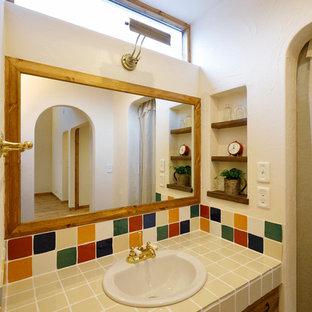 他の地域のカントリー風おしゃれなトイレ・洗面所 (フラットパネル扉のキャビネット、中間色木目調キャビネット、白い壁、オーバーカウンターシンク、タイルの洗面台、茶色い床、ベージュのカウンター) の写真