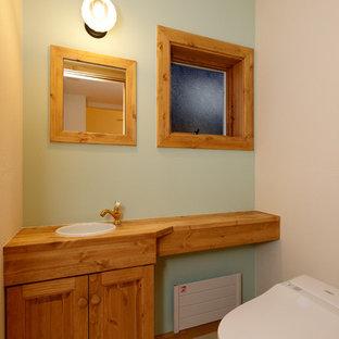 他の地域のカントリー風おしゃれなトイレ・洗面所 (レイズドパネル扉のキャビネット、中間色木目調キャビネット、青い壁、オーバーカウンターシンク、木製洗面台、ベージュの床、ブラウンの洗面カウンター) の写真
