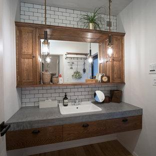 東京23区のインダストリアルスタイルのおしゃれなトイレ・洗面所 (白い壁、無垢フローリング、オーバーカウンターシンク、コンクリートの洗面台、茶色い床、グレーの洗面カウンター) の写真