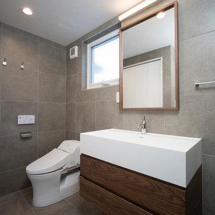 東京23区のミッドセンチュリースタイルのおしゃれなトイレ・洗面所 (フラットパネル扉のキャビネット、中間色木目調キャビネット、グレーの壁、一体型シンク、グレーの床) の写真