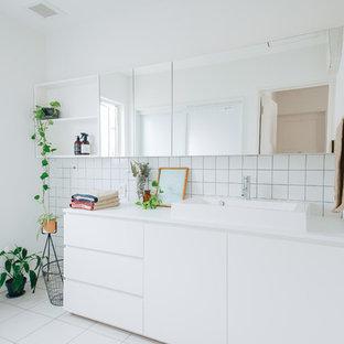 他の地域の北欧スタイルのおしゃれなトイレ・洗面所 (フラットパネル扉のキャビネット、白いキャビネット、白いタイル、磁器タイル、白い壁、磁器タイルの床、ベッセル式洗面器、白い床、白い洗面カウンター) の写真