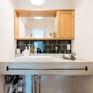 他の地域のインダストリアルスタイルのおしゃれなトイレ・洗面所 (オープンシェルフ、黒いタイル、磁器タイル、白い壁、濃色無垢フローリング、コンクリートの洗面台、グレーの洗面カウンター) の写真