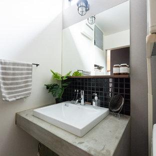 他の地域のインダストリアルスタイルのおしゃれなトイレ・洗面所 (黒いタイル、磁器タイル、白い壁、ベッセル式洗面器、コンクリートの洗面台、グレーの洗面カウンター) の写真