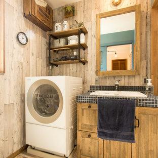 他の地域のラスティックスタイルのおしゃれなトイレ・洗面所 (落し込みパネル扉のキャビネット、中間色木目調キャビネット、グレーの壁、オーバーカウンターシンク、タイルの洗面台、マルチカラーの床) の写真