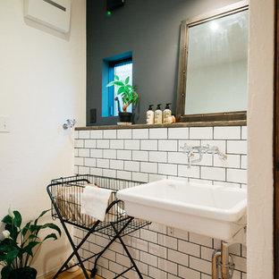 他の地域のミッドセンチュリースタイルのおしゃれなトイレ・洗面所 (マルチカラーの壁、無垢フローリング、壁付け型シンク、茶色い床) の写真