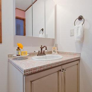 名古屋のおしゃれなトイレ・洗面所 (白いキャビネット、ピンクの洗面カウンター) の写真