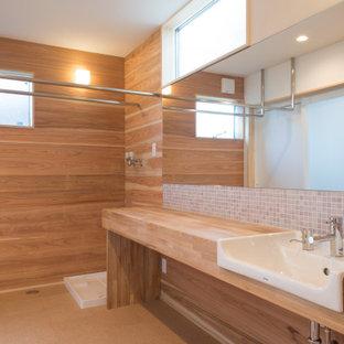 Cette photo montre un grand WC et toilettes moderne en bois avec des portes de placard marrons, des carreaux de porcelaine, un mur blanc, un sol en liège, une vasque, un plan de toilette en bois, un sol marron, un plan de toilette marron, meuble-lavabo encastré et un plafond en papier peint.