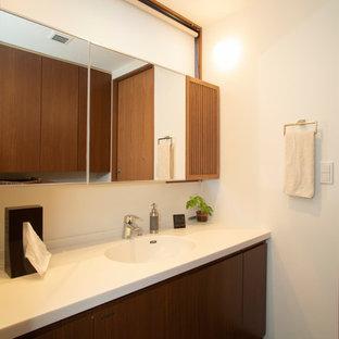 他の地域のミッドセンチュリースタイルのおしゃれなトイレ・洗面所 (フラットパネル扉のキャビネット、中間色木目調キャビネット、白い壁、一体型シンク、グレーの床) の写真
