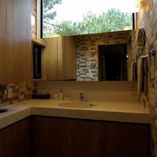 他の地域のミッドセンチュリースタイルのおしゃれなトイレ・洗面所 (茶色いキャビネット、ベージュのタイル、トラバーチンタイル、ベージュの壁、一体型シンク、人工大理石カウンター、白い洗面カウンター、クッションフロア、茶色い床) の写真