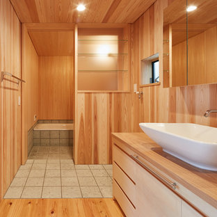 東京23区の中くらいの和風のおしゃれなトイレ・洗面所 (インセット扉のキャビネット、ベージュのキャビネット、一体型トイレ、ベージュのタイル、淡色無垢フローリング、木製洗面台、茶色い床、ブラウンの洗面カウンター、茶色い壁、ベッセル式洗面器) の写真
