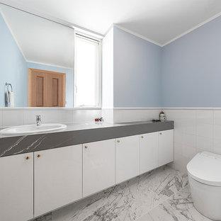 エクレクティックスタイルのおしゃれなトイレ・洗面所 (フラットパネル扉のキャビネット、白いキャビネット、一体型トイレ、白いタイル、青い壁、マルチカラーの床、グレーの洗面カウンター、オーバーカウンターシンク) の写真