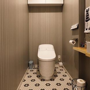 Пример оригинального дизайна интерьера: туалет среднего размера в стиле модернизм с плоскими фасадами, белыми фасадами, унитазом-моноблоком, серыми стенами, полом из винила, настольной раковиной, столешницей из дерева, разноцветным полом и белой столешницей