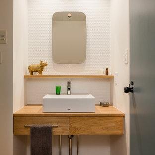 Esempio di un piccolo bagno di servizio minimalista con nessun'anta, ante marroni, piastrelle bianche, piastrelle a mosaico, pareti bianche, pavimento in legno massello medio, lavabo a bacinella, top in legno, pavimento marrone e top marrone