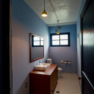Foto de aseo asiático con armarios con paneles lisos, puertas de armario de madera oscura, sanitario de una pieza, lavabo sobreencimera, encimera de madera, suelo beige, paredes azules y encimeras marrones