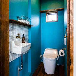 他の地域の小さいコンテンポラリースタイルのおしゃれなトイレ・洗面所 (茶色いキャビネット、一体型トイレ、白いタイル、モザイクタイル、青い壁、濃色無垢フローリング、茶色い床) の写真