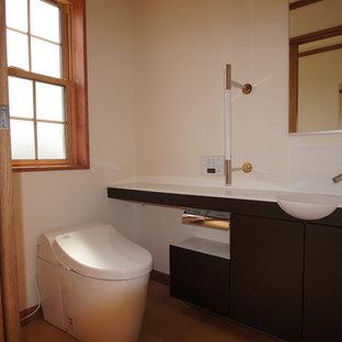 Foto di un bagno di servizio minimal con ante lisce, ante in legno scuro, WC monopezzo, pareti bianche, pavimento in terracotta, lavabo integrato, top in onice, pavimento marrone e top multicolore