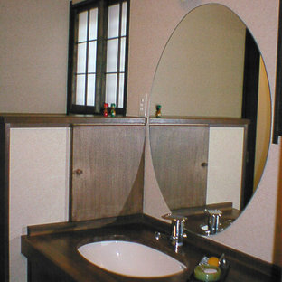 Asiatische Gästetoilette mit verzierten Schränken, dunklen Holzschränken, weißen Fliesen, dunklem Holzboden, Waschtisch aus Holz, lila Boden und lila Waschtischplatte in Tokio