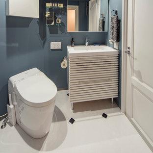 На фото: туалет в морском стиле с фасадами с филенкой типа жалюзи, белыми фасадами, синими стенами, полом из керамической плитки, монолитной раковиной и разноцветным полом с