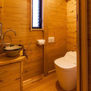 Ejemplo de aseo asiático con armarios con paneles lisos, puertas de armario de madera oscura, paredes marrones, suelo de madera en tonos medios, lavabo sobreencimera, encimera de madera, suelo marrón y encimeras marrones