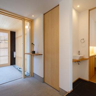 他の地域の和風のおしゃれなトイレ・洗面所 (フラットパネル扉のキャビネット、中間色木目調キャビネット、白い壁、コンクリートの床、ベッセル式洗面器、木製洗面台、グレーの床、ブラウンの洗面カウンター) の写真