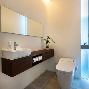 他の地域のコンテンポラリースタイルのおしゃれなトイレ・洗面所 (白い壁、コンクリートの床、グレーの床、フラットパネル扉のキャビネット、濃色木目調キャビネット、壁掛け式トイレ、ベッセル式洗面器、木製洗面台) の写真