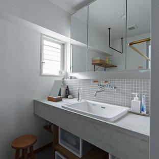 Réalisation d'un petit WC et toilettes design avec un placard sans porte, un carrelage gris, carrelage en mosaïque, un mur blanc, un plan de toilette gris, des portes de placard en bois brun, béton au sol, un lavabo posé, un plan de toilette en béton et un sol gris.
