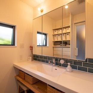 Idée de décoration pour un petit WC et toilettes urbain avec un mur blanc, béton au sol, un sol gris, un placard à porte vitrée, des portes de placard blanches, un carrelage bleu, un carrelage métro, un plan de toilette en surface solide, un plan de toilette blanc et un lavabo encastré.