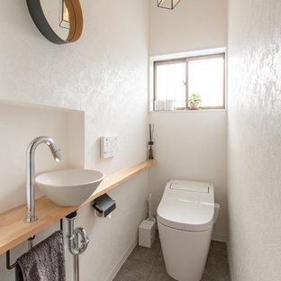 Ispirazione per un piccolo bagno di servizio industriale con pareti bianche, pavimento in cemento, lavabo a bacinella, pavimento grigio, top in legno, soffitto in carta da parati e carta da parati