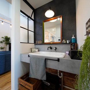 他の地域のビーチスタイルのおしゃれなトイレ・洗面所 (グレーの壁、無垢フローリング、オーバーカウンターシンク、茶色い床) の写真