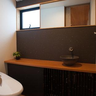 Foto de aseo de estilo zen con armarios tipo mueble, puertas de armario negras, sanitario de una pieza, paredes negras, suelo de baldosas de cerámica, lavabo sobreencimera y encimera de laminado