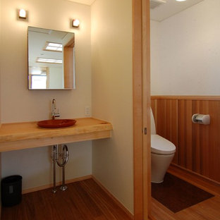 Ejemplo de aseo asiático, pequeño, con sanitario de dos piezas, paredes blancas, suelo de madera en tonos medios, lavabo encastrado, encimera de madera, suelo marrón y encimeras beige