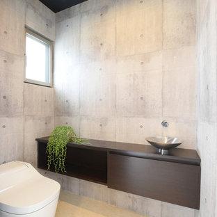 他の地域のモダンスタイルのおしゃれなトイレ・洗面所 (フラットパネル扉のキャビネット、濃色木目調キャビネット、グレーの壁、ベッセル式洗面器、ベージュの床、木製洗面台、一体型トイレ、ブラウンの洗面カウンター) の写真