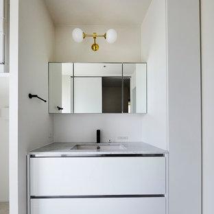 他の地域のモダンスタイルのおしゃれなトイレ・洗面所 (フラットパネル扉のキャビネット、白いキャビネット、白い壁、一体型シンク、グレーの床) の写真